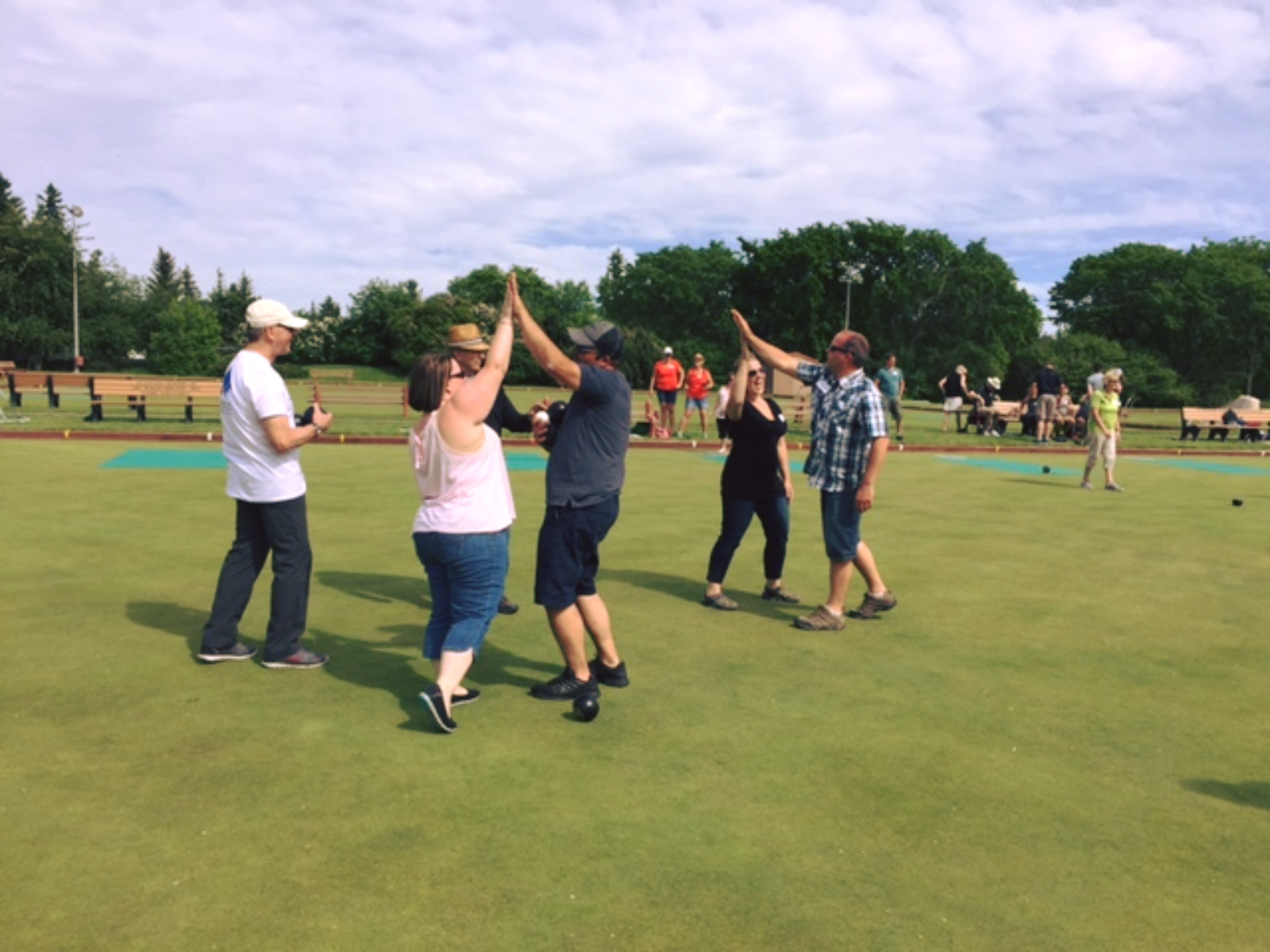 Lawn bowlers high-fiving on a green