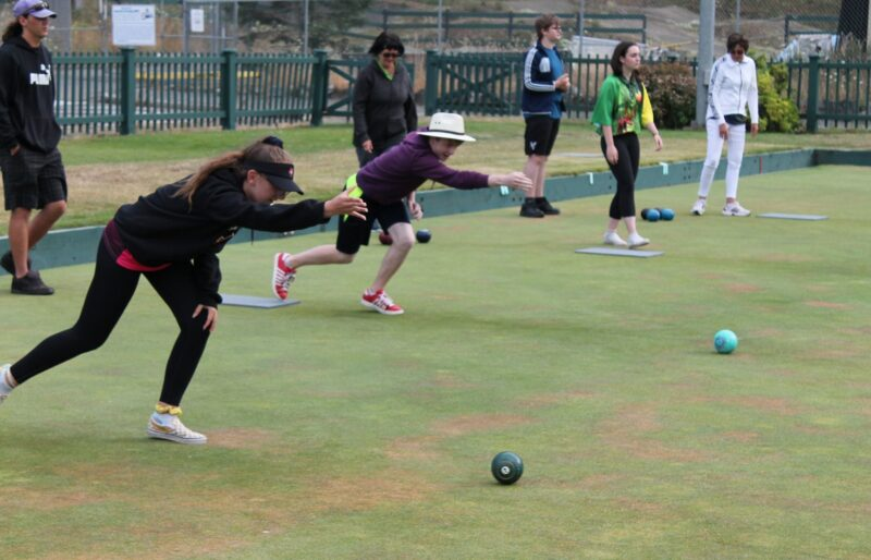 Youth bowlers rolling bowls