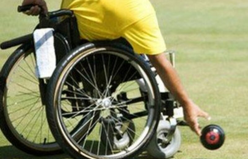 Person in a wheelchair rolling a lawn bowl