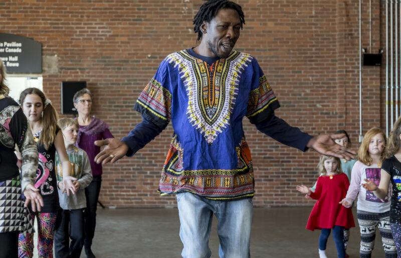 Des enfants de tous âges dansent, alignés en deux rangées aux côtés d'un danseur, tout en suivant attentivement les instructions.