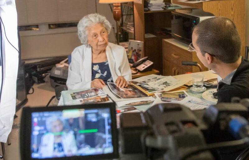 Une femme est debout à un bureau avec des photos rassemblées devant elle et elle parle à un historien oral du Musée qui lui fait face. La conversation est enregistrée avec une caméra.