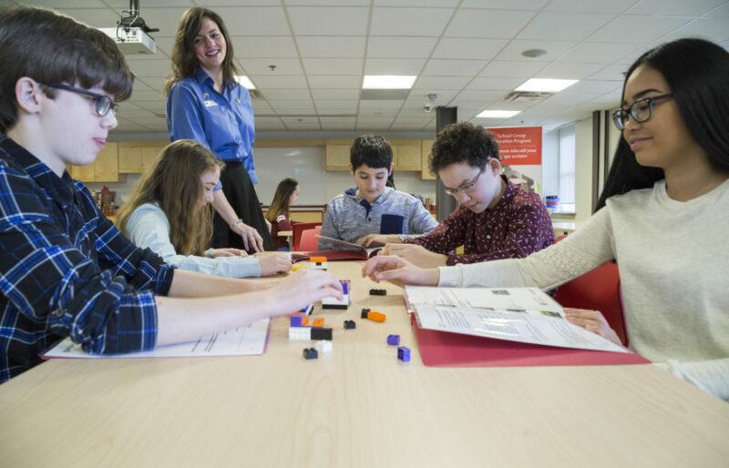 Des élèves sont assis face à face à une table dans la salle de classe du Musée, tandis qu'un interprète du patrimoine les guide à travers l'un des programmes éducatifs utilisant des blocs Lego.