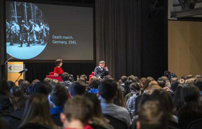 Un homme et une femme sont assis sur scène devant une foule.