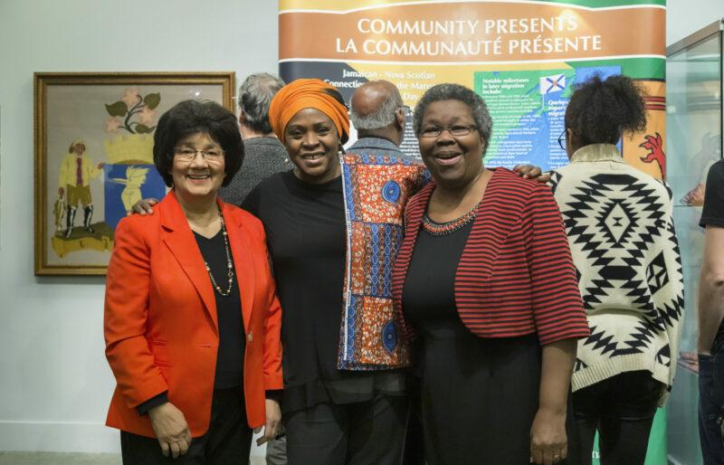 Trois femmes sont serrées l'une contre l'autre, souriant à la caméra, devant une exposition. Trois visiteurs sont à l'arrière-plan en train de lire l'information de l'exposition.