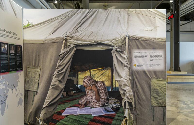 Un grand panneau grandeur nature d'une exposition montre l'image d'une jeune femme qui fait ses devoirs assise sur le sol d'une tente pour réfugiés.