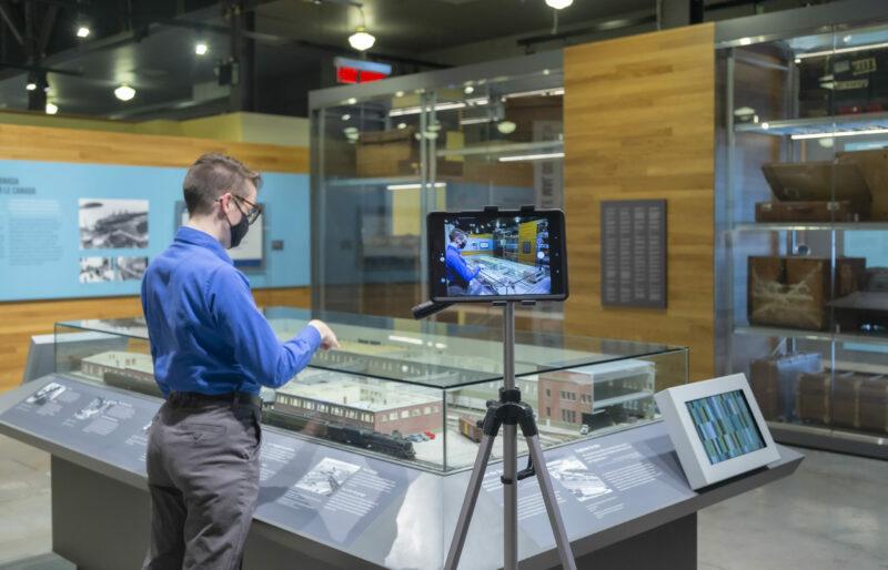 Un interprète du patrimoine se tient devant la maquette du hangar d'immigration du Quai 21 tandis qu'un iPad enregistre sa présentation.