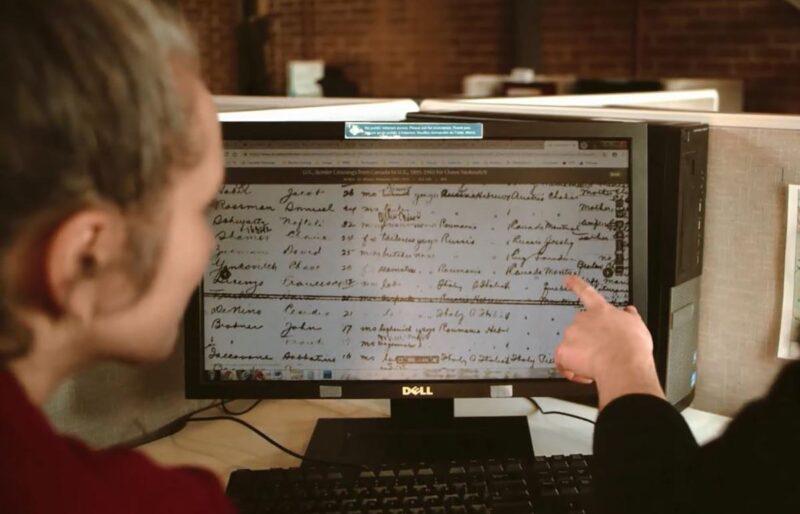 Une femme regarde un écran d'ordinateur montrant le dossier d'immigration de sa famille, tandis qu'un de nos chercheurs montre un mot spécifique sur l'écran pendant une recherche généalogique familiale.
